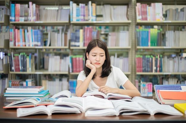 Livro de leitura aborrecido do estudante de mulher asiático na biblioteca com muitos livros na universidade.