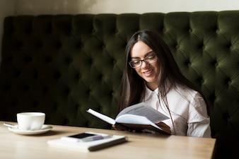 Livro de leitura alegre menina no café