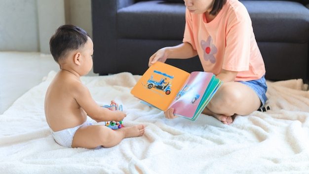 Livro de leitura asiática da mãe com seu filho