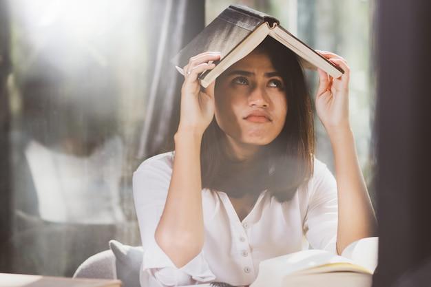Livro de leitura asiático da mulher e trabalho com perfuração.