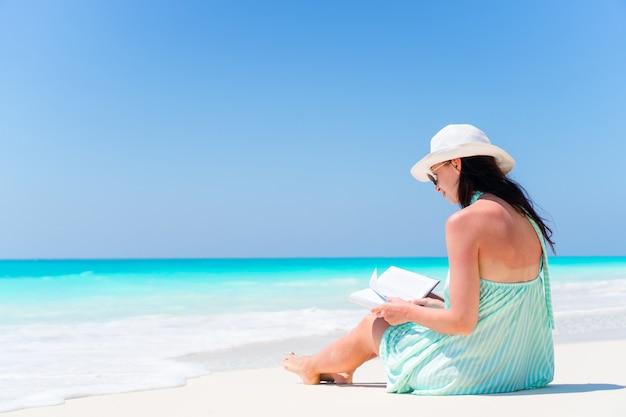 Livro de leitura da jovem mulher durante a praia branca tropical