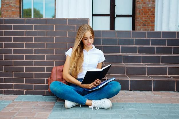 Livro de leitura da jovem mulher nas escadas da universidade, preparando-se para exames na faculdade.