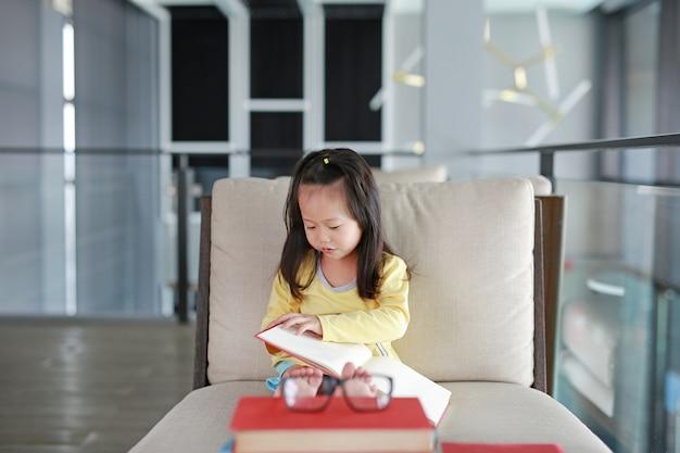 Livro de leitura da menina da criança pequena na biblioteca, conceito da educação.