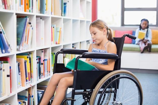 Livro de leitura da menina da escola com deficiência na biblioteca