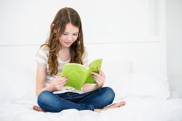 Livro de leitura da menina na cama em casa