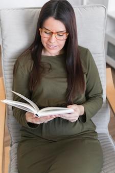 Livro de leitura da mulher sentada na cadeira