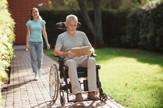 Livro de leitura de homem inválido de reabilitação ao ar livre