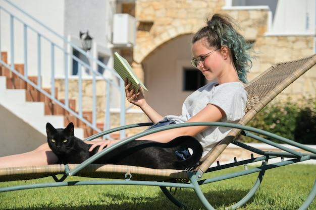 Livro de leitura de menina adolescente com gato doméstico preto a descansar