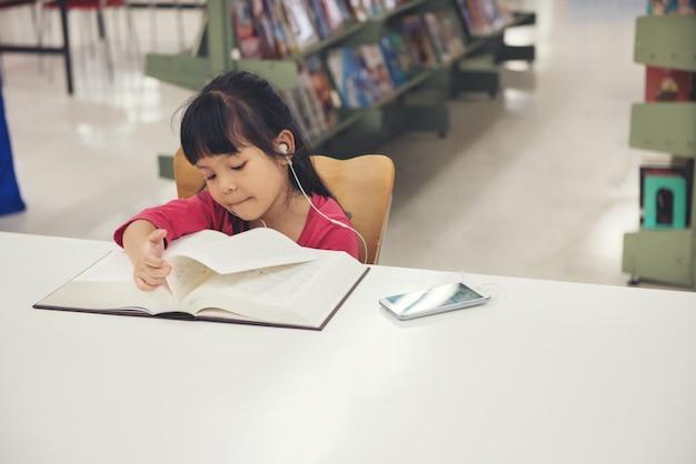 Livro de leitura de menina de crianças na sala da biblioteca