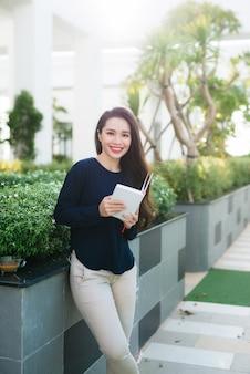Livro de leitura de menina jovem e bonita no parque em um dia ensolarado.