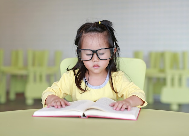 Livro de leitura de menina pequena criança na biblioteca