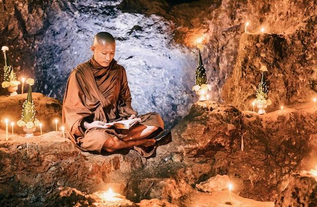 Livro de leitura de monge dentro da caverna, tailândia