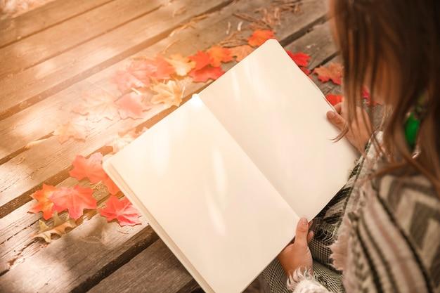 Livro de leitura de mulher anônima no parque outono