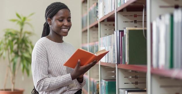 Livro de leitura de mulher de tiro médio