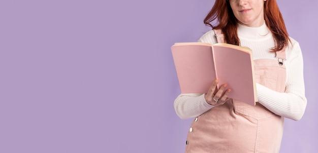 Livro de leitura de mulher grávida de close-up
