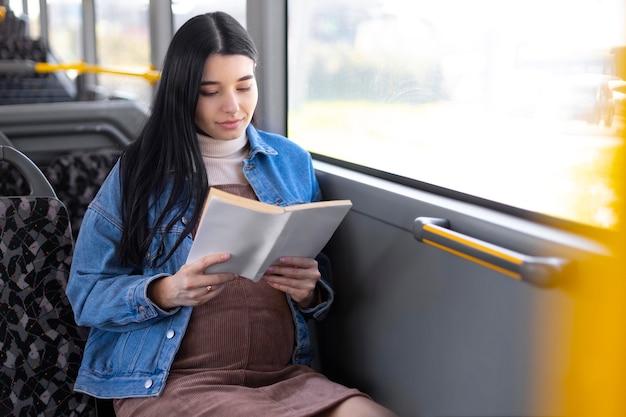 Livro de leitura de mulher grávida de tiro médio