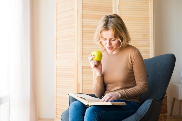 Livro de leitura de mulher loira enquanto come maçã