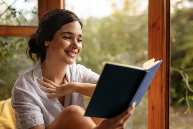 Livro de leitura de mulher sorridente em plano médio
