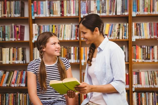 Livro de leitura de professor e menina na biblioteca