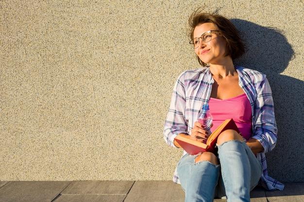 Livro de leitura de sorriso da água bebendo da mulher.