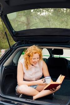 Livro de leitura de sorriso da jovem mulher na viagem