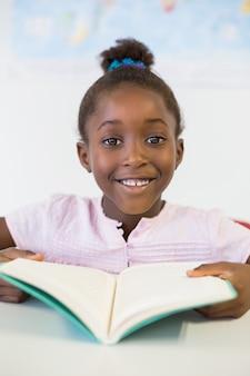 Livro de leitura de sorriso da menina da escola na sala de aula