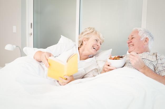 Livro de leitura do casal sênior na cama