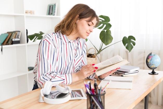 Livro de leitura do estudante feminino no gabinete