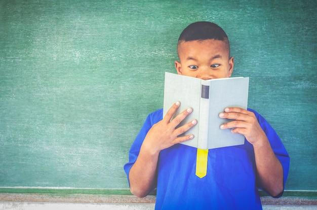 Livro de leitura do estudante rural asiática na frente do quadro-negro