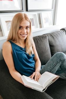 Livro de leitura feliz e atraente jovem womna em casa