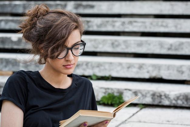Livro de leitura feminino concentrado nas escadas