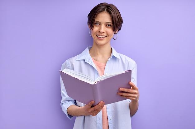 Livro de leitura feminino confiante isolado no fundo roxo, mulher jovem em roupas casuais, olhando para ca ...