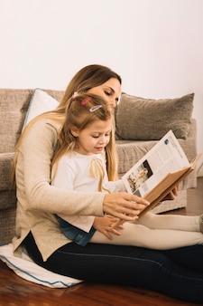Livro de leitura feminino jovem com a filha no chão