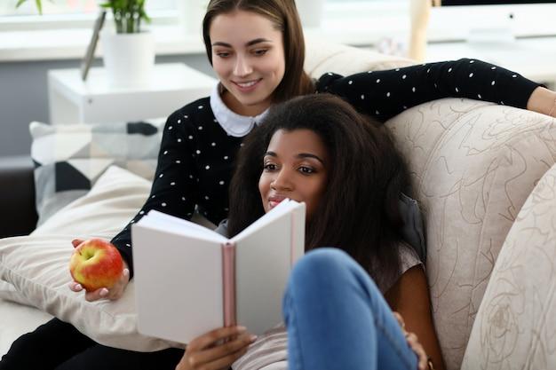 Livro de leitura frend de duas mulheres sentar no treinador contra