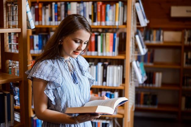 Livro de leitura inteligente menina jovem estudante na biblioteca