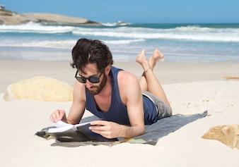 Livro de leitura jovem bonito na praia