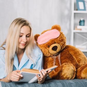 Livro de leitura jovem com brinquedo macio na cama