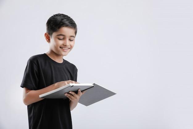 Livro de leitura pequeno indiano / asiático menino bonito isolado