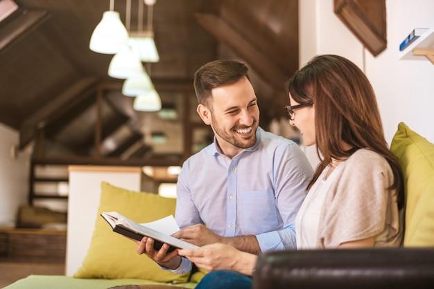Livro de leitura relaxado jovem casal no sofá em casa