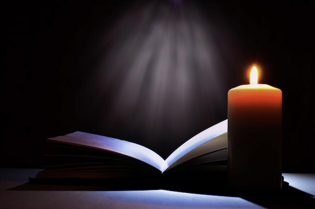 Livro de magia e vela. livro da bíblia e luz misteriosa.