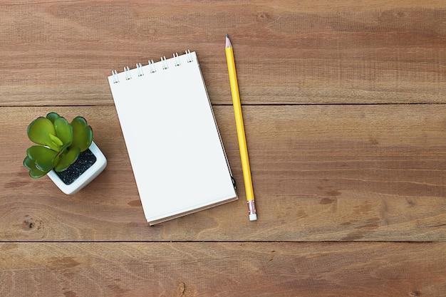 Livro de nota com o lápis na mesa de madeira do escritório. vista do topo.