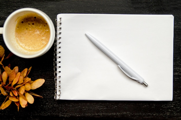 Livro de nota de papel em branco com lápis e café na mesa preta
