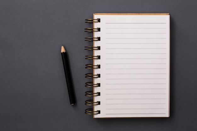 Livro de nota e pecil em fundo preto