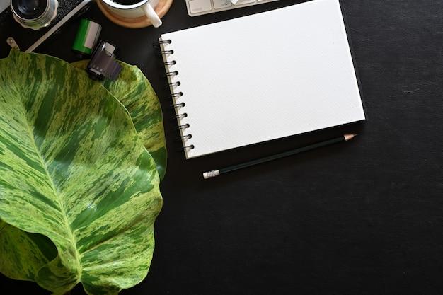 Livro de nota em branco aberto, local de trabalho do fotógrafo com fundo escuro de couro e espaço de cópia