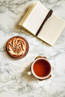 Livro de nota em branco, uma xícara de chá e bolo.