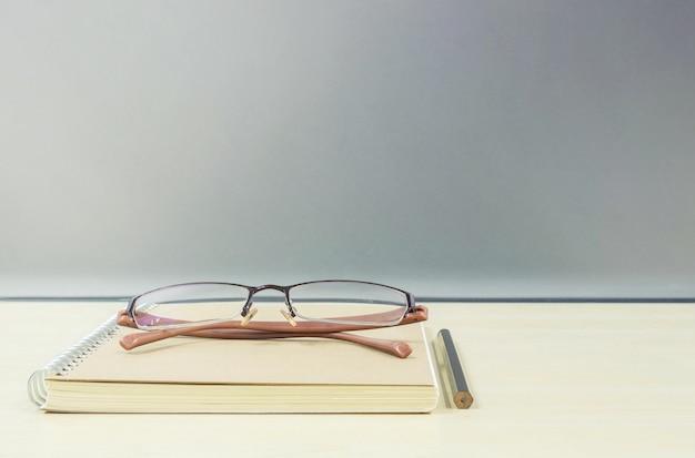 Livro de nota marrom closeup na mesa de madeira turva e parede de vidro fosco texturizada