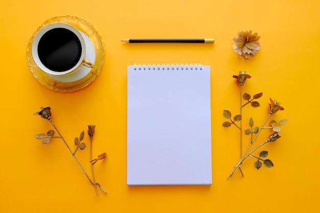 Livro de notas em branco com café preto, lápis e flor de ouro em fundo laranja