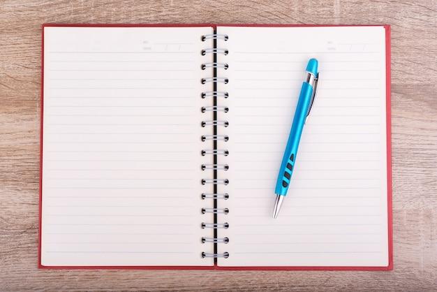 Livro de notas ou diário e caneta azul colocados na mesa de madeira.