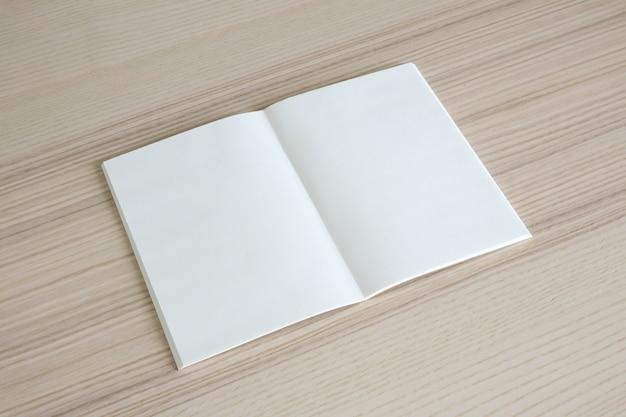 Livro de papel aberto em branco na mesa de madeira