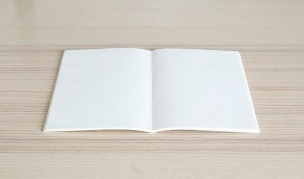 Livro de papel aberto em branco no fundo da mesa de madeira